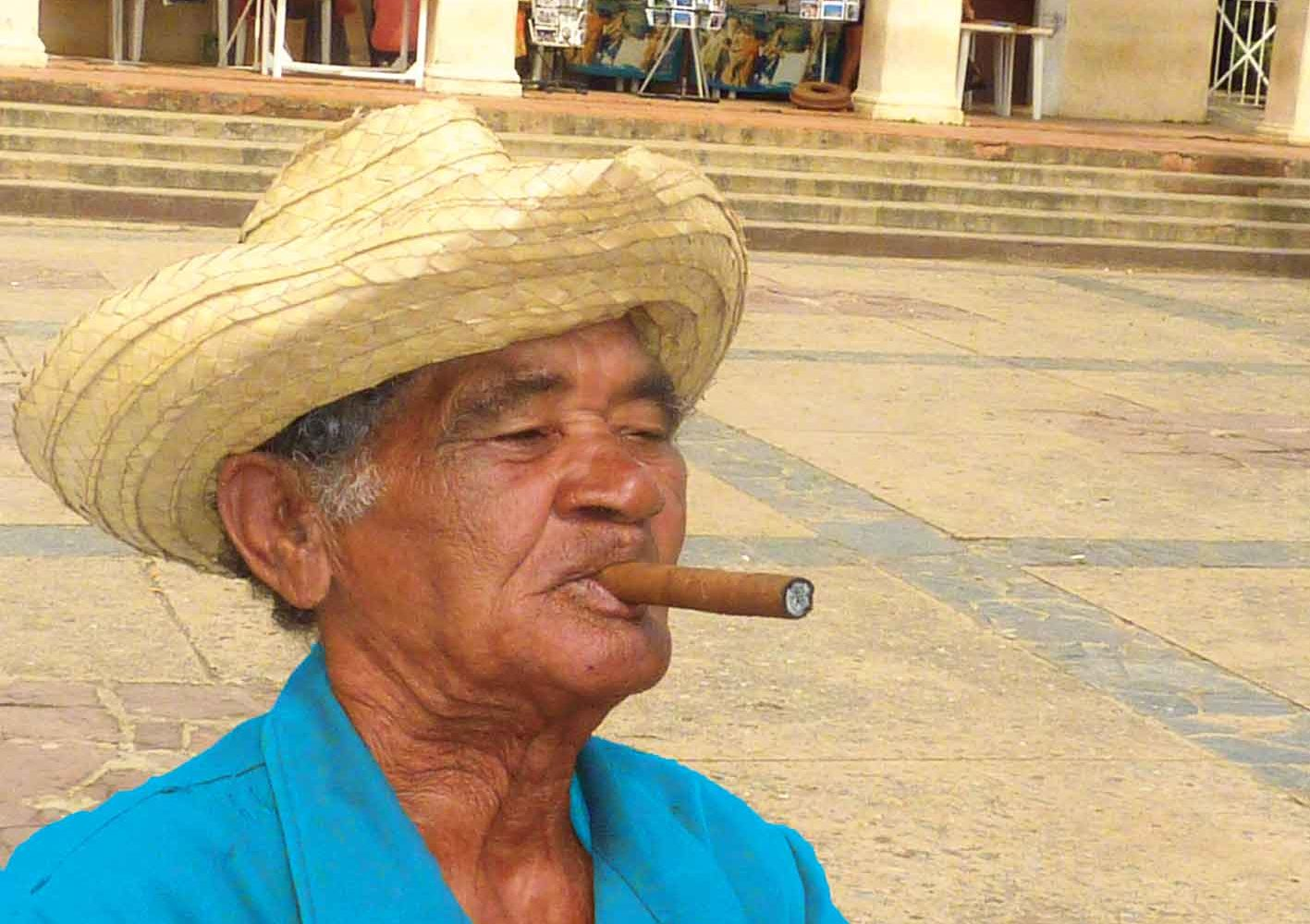 Typische Reiseimpression aus Kuba - ein Einheimischer raucht eine Zigarre