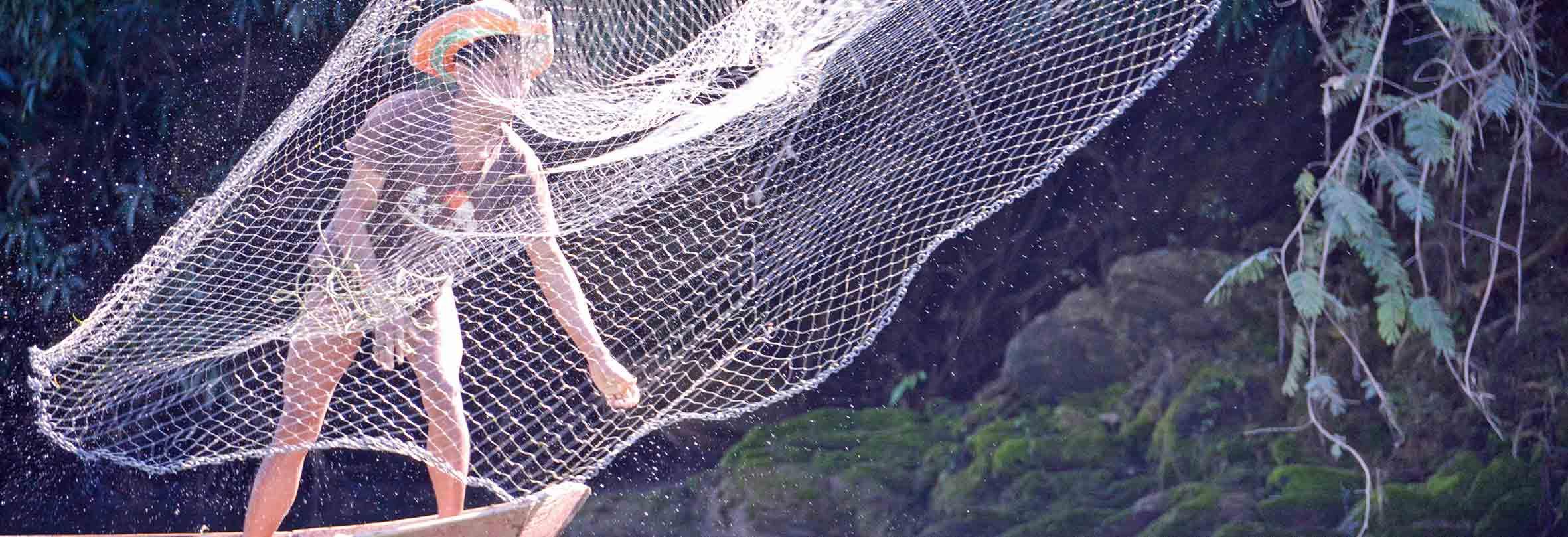 Ein Fischer wirft sein Netz aus, Laos